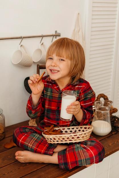 Ragazzo che mangia i biscotti di natale e che beve latte Foto Gratuite