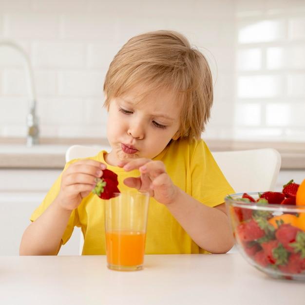 Ragazzo che mangia frutta Foto Gratuite