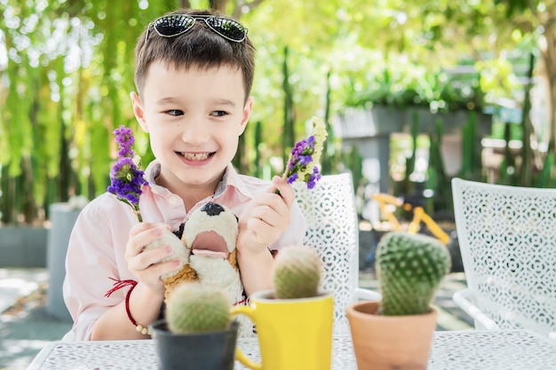 Boy enjoy playing with flower and cactus in a restaurant - boy happy with nature concept Free Photo