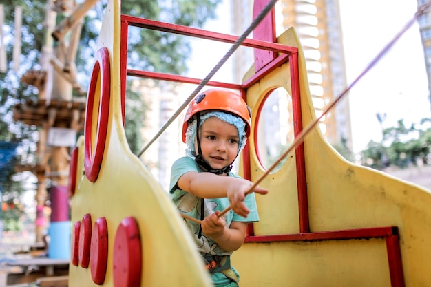 Boy enjoying time in a rope structure at adventure park Premium Photo
