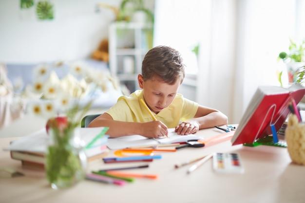 熱心にテーブルで書いたり描いたりする少年 Premium写真