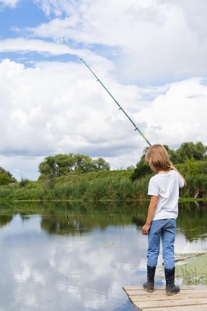 Мальчик рыбачит на деревянном мосту у пруда Premium Фотографии