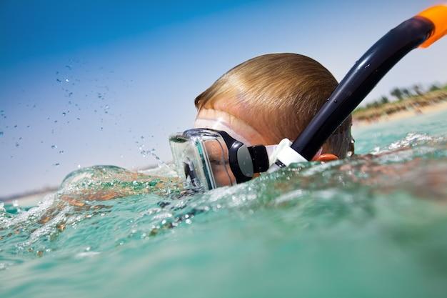 Мальчик плавает в море Premium Фотографии