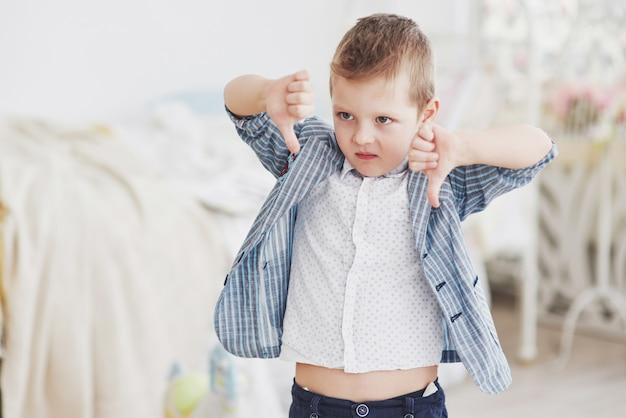 少年は指を下に振ります。感情の概念。レッスンや学校に対する彼の態度を示しています Premium写真