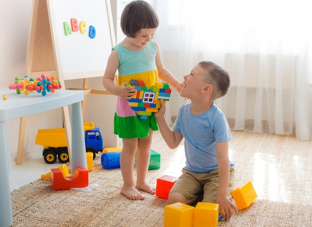 Boy and girl are holding heart made plastic blocks. brother sister have fun playing together in the room. Premium Photo