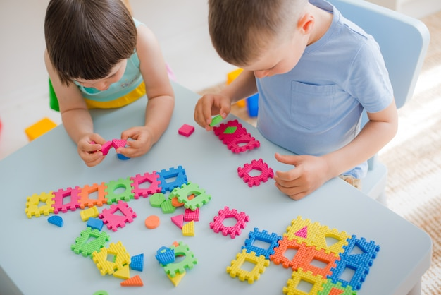 A boy and a girl collect a soft puzzle at the table Premium Photo