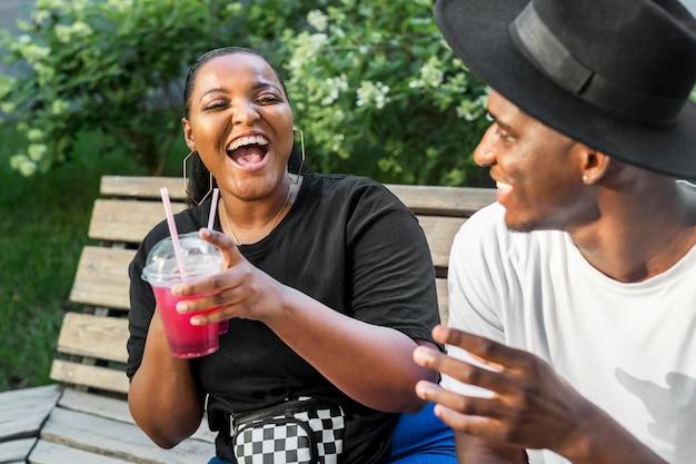 Ragazzo e ragazza che godono di alcuni frullati all'aperto Foto Gratuite