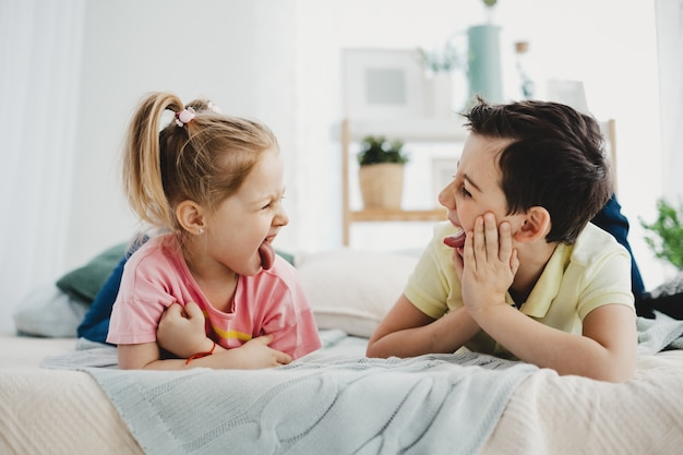 Boy and girl grimace to each other lying on the bed Free Photo