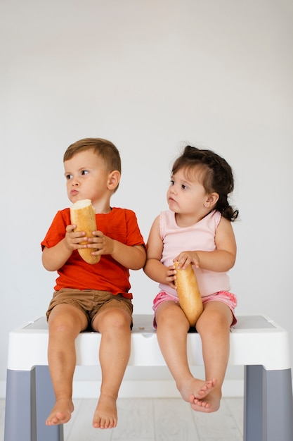 Boy and girl sitting on a table and eating bread Free Photo