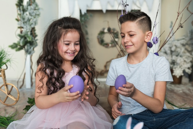Boy and girl sitting with easter eggs Free Photo