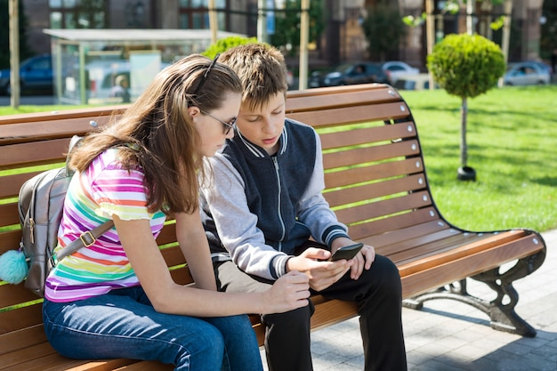 Boy and girl teenagers play, look at the smartphone Premium Photo