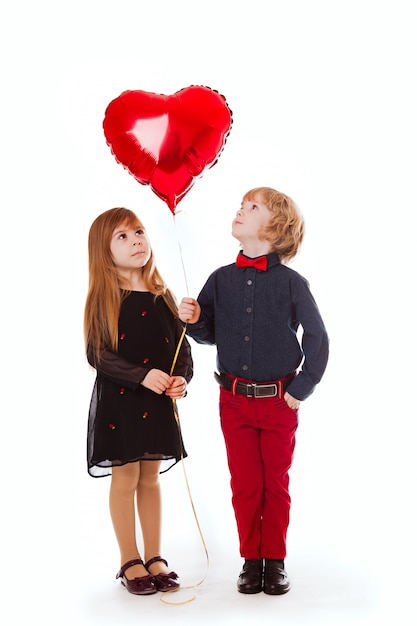 Boy and girl on a white background holding a balloon red heart Premium Photo