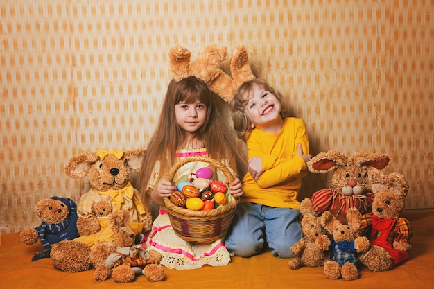 Boy and girl with rabbit ears sitting around a lot of straw and plush hares, vintage style. Premium Photo