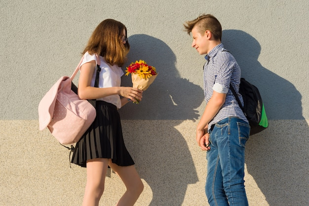Boy gives girl bouquet of flowers. outdoor portrait of couple teenagers. Premium Photo