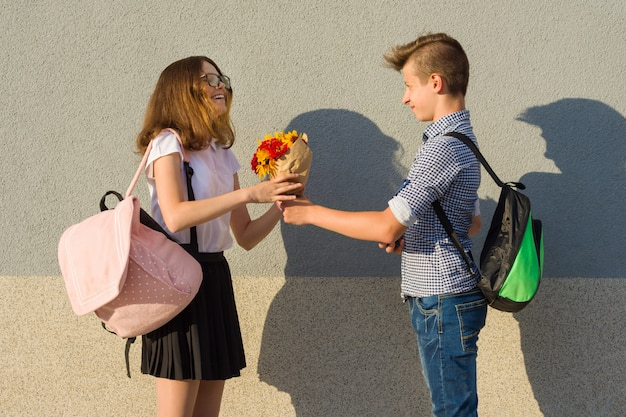 Boy gives girl bouquet of flowers Premium Photo