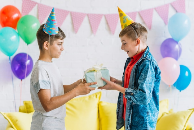 Boy giving birthday gift to his friend Free Photo
