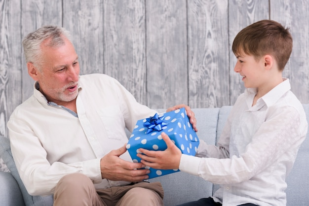 Boy giving blue wrapped birthday gift box to his grandfather Free Photo