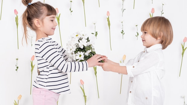 Boy giving flowers to cute girl Free Photo