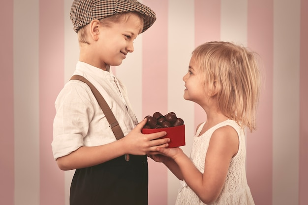 Boy giving a girl box full of chocolates Free Photo