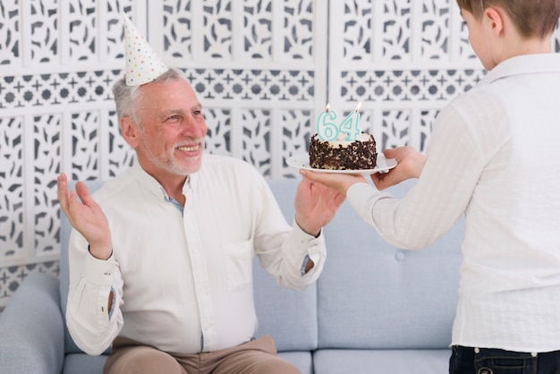 Boy giving surprised birthday cake to his happy grandfather sitting on sofa Free Photo