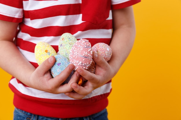Boy hands holding bunch of colorful easter eggs Free Photo
