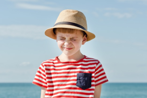 Boy in hat squinting from the sun. sea on background Premium Photo