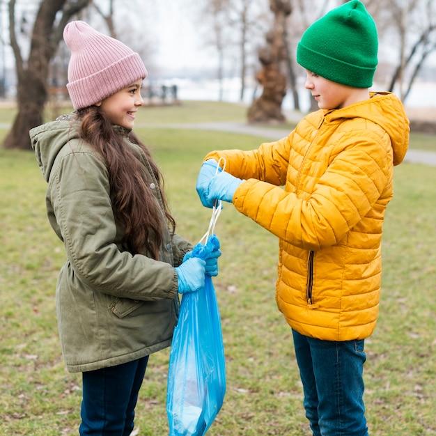 Ragazza di aiuto del ragazzo che fa un nodo sul sacchetto di plastica Foto Gratuite