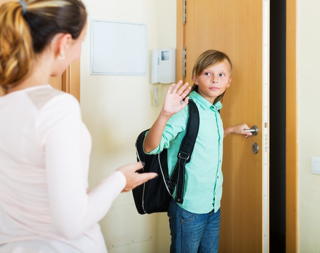 Boy and his mother staying near flat entrance Free Photo