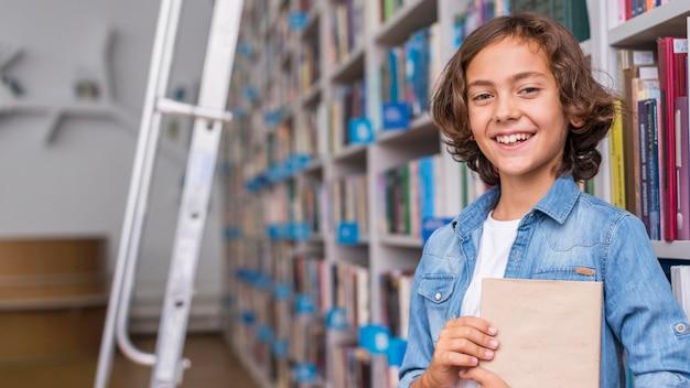 Мальчик держит книгу с копией пространства Бесплатные Фотографии