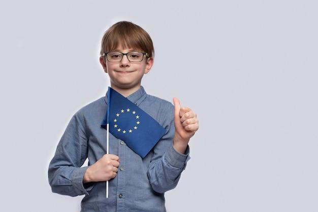 Мальчик держит флаг ес и показывает хорошо сделанный жест Premium Фотографии