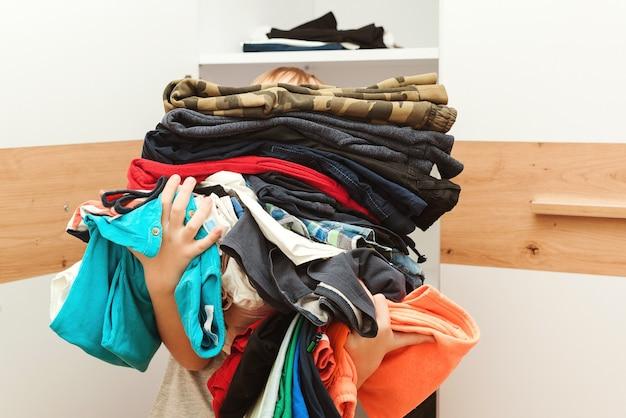 巨大な服の山を持っている少年。子供はクローゼットの中で注文します。ストレージ組織。再利用、再販、リサイクル、寄付のための中古子供服。 Premium写真