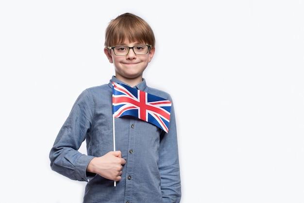 Мальчик держит флаг великобритании Premium Фотографии