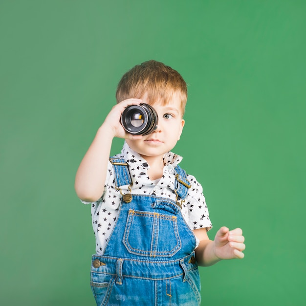 Boy holding camera lens at eye Free Photo