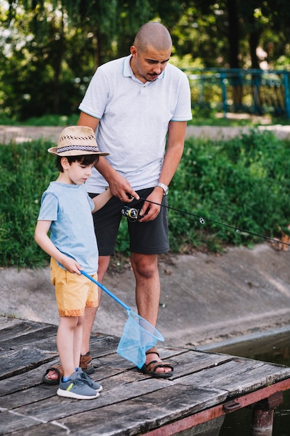 Boy holding fishing net standing with his father on pier Free Photo
