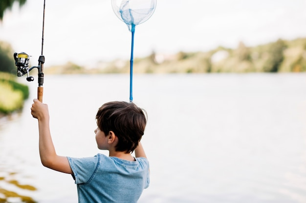 Boy holding fishing rod and net near lake Free Photo