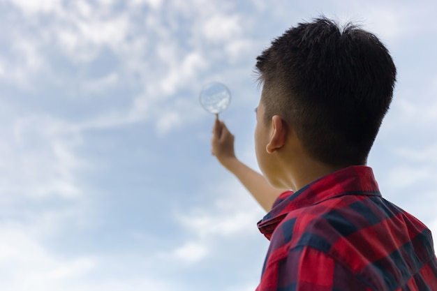 Boy holding a magnifying glass and looking to the sky Premium Photo