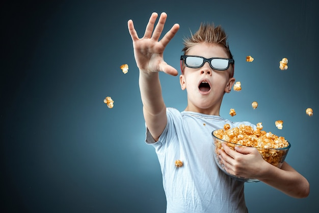 A boy holding popcorn in his hands watching a movie in 3d glasses, fear, blue wall. the concept of a cinema, films, emotions, surprise, leisure. streaming platforms. Premium Photo