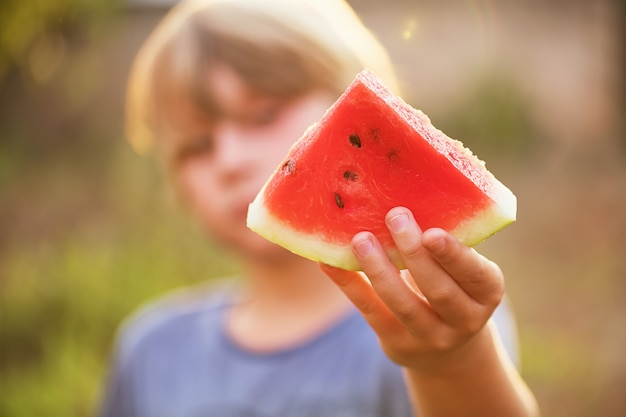 The boy holds a piece of watermelon in his hand and holds it out, selective focus, lens effect. summer concept, fresh and happy. Premium Photo