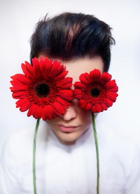 Boy holds red flowers before his eyes Premium Photo