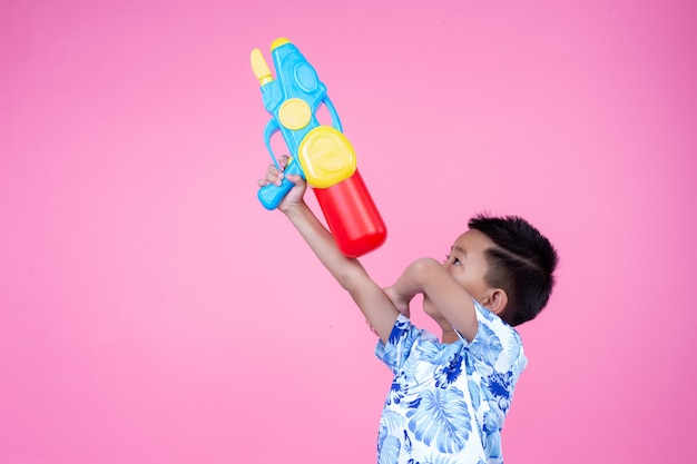The boy holds a water gun on a pink background. Free Photo