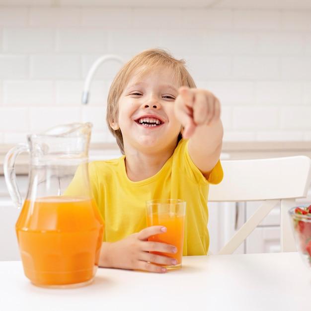 Ragazzo a casa nell'indicare della cucina Foto Gratuite