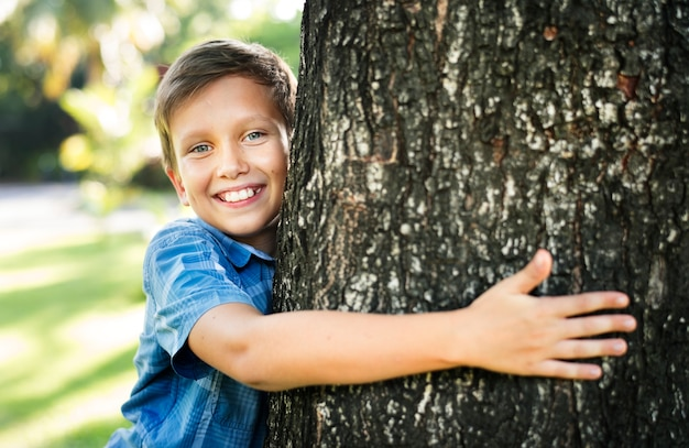 Boy hugging a big tree in the park Free Photo