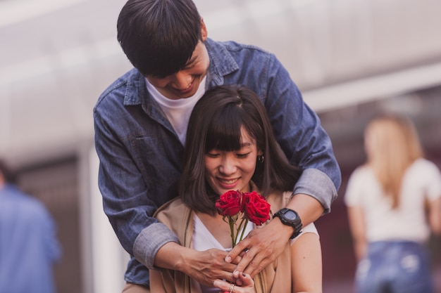 Boy hugging behind his girlfriend and giving her roses Free Photo