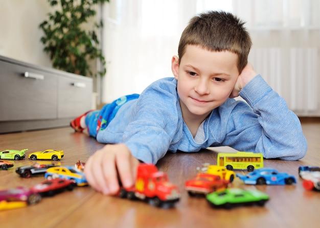 木製の床に横になっている青いセーターの少年 Premium写真