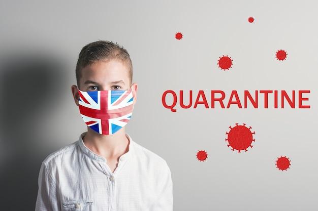 明るい背景に彼の顔にイングランドの旗を持つ医療マスクの少年。 Premium写真