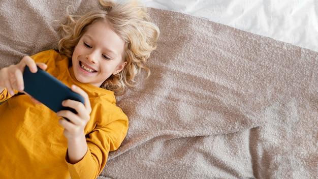 모바일에서 재생하는 침대에서 소년 무료 사진
