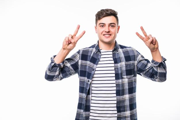 両手に勝利のピースサインを示す勝利を祝う暗いtショートの少年 無料写真