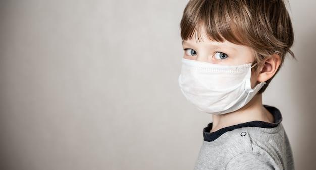 医療マスクの少年。コロナウイルスcovid-19ロックダウン、パニック。新しいウイルスからのワクチン Premium写真