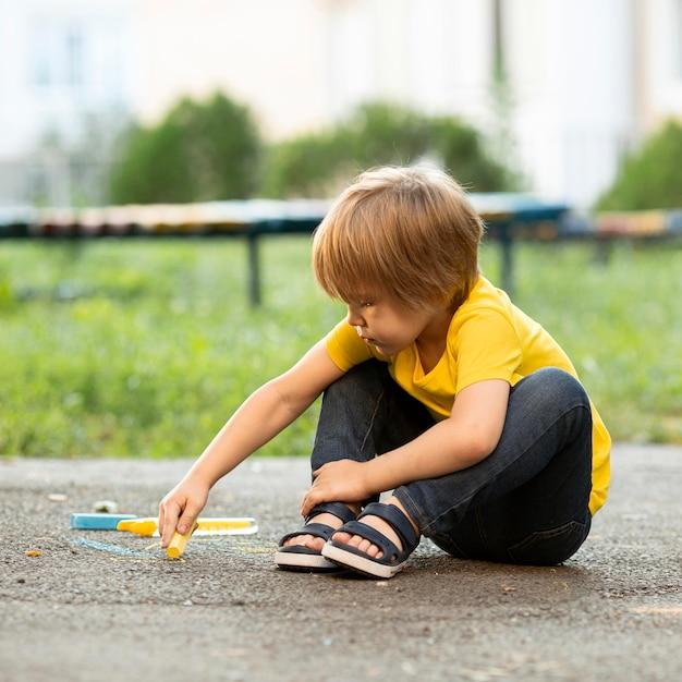 Мальчик в парке, рисование мелом Бесплатные Фотографии