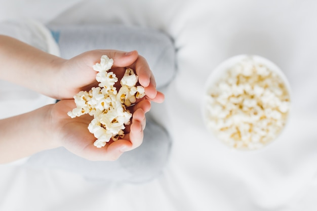 Boy is holding a handful of popcorn close-up Premium Photo